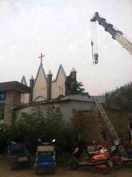 Una gru si appresta a togliere la croce da una chiesa di Zhoushan (Zhejiang)