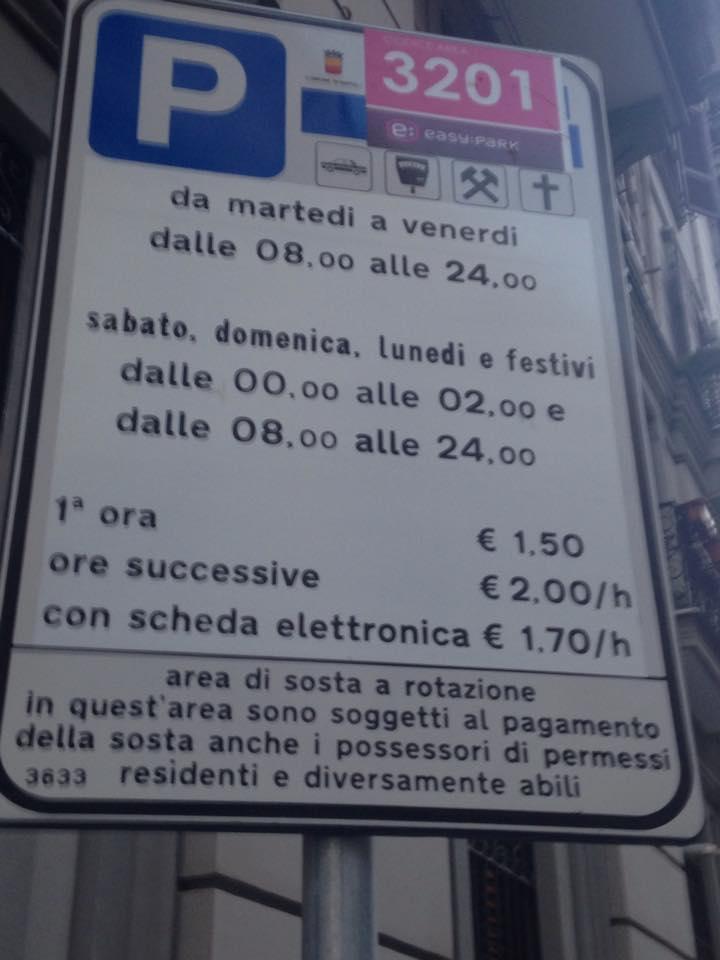 La segnaletica modificata nottetempo (col bollino rosa in alto a destra) per trasformare i parcheggi in area a pagamento per tutti