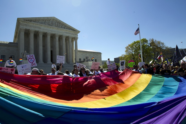 Demonstrators stand in front of a rainbow flag of the Supreme Court in Washington, Tuesday, April 28, 2015. The Supreme Court is set to hear historic arguments in cases that could make same-sex marriage the law of the land. The justices are meeting Tuesday to offer the first public indication of where they stand in the dispute over whether states can continue defining marriage as the union of a man and a woman, or whether the Constitution gives gay and lesbian couples the right to marry. (AP Photo/Jose Luis Magana)