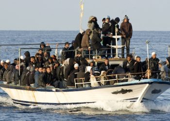 FILE -- In this March 7, 2011 file photo, a boat loaded with migrants is spotted at sea off the Sicilian island of Lampedusa, Italy. The odyssey often begins in an Eritrean refugee camp in Sudan where smugglers offer a deal too good to refuse: Transport to Libya and the chance of a boat trip to Europe, sometimes with no money down. But once in the lawlessness of Libya, the desperate and the dreamers are essentially held hostage by their traffickers until payments are extorted from relatives or they come up with the cash themselves. (AP Photo/Antonello Nusca, File)