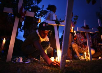 epa04695974 Kenya Red Cross team members light candles among crosses on the ground as they attend the second day of candlelight vigil held for the 148 people killed in an attack on Garissa University College in Garissa town, in downtown Nairobi, Kenya, 08 April 2015. Hundreds of Kenyans continue to gather in solidarity to mourn the loss of their countrymen while five terror suspects were arraigned in a Nairobi court on 07 April for supplying attackers with guns used in an attack. Kenyan government on 08 April froze 85 bank accounts linked to suspected supporters of al-Shabab.  EPA/DANIEL IRUNGU