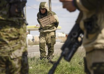 """FILE - In this Thursday, April 23, 2015 file photo, a man with a poster around his neck reading """"I am marauder, I beat and steal from civilians"""" is tied to a post by pro-Russian rebels who accused him of stealing from local people, next to a highway in Krasnyi Partyzan, Ukraine. (AP Photo/Mstyslav Chernov, File)"""