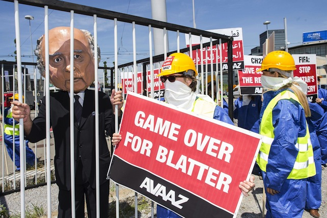 epa04772330 An activist wears a giant head depicting FIFA President Joseph Blatter inside a cage during a protest by the Avaaz.org organisation prior to the 65th FIFA Congress at the Hallenstadion in Zurich, Switzerland, 28 May 2015. The 65th FIFA Congress with the president's election will take place on 29 May 2015 in Zurich. Avaaz.org asks Blatter to be held accountable for the corruption he has made possible at FIFA.  EPA/ENNIO LEANZA