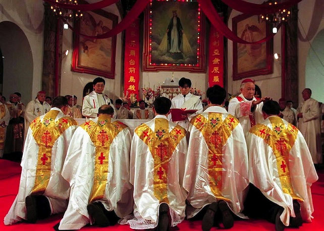 BEJ51 - 20000106 - BEIJING, CHINA : Five bishops go on their knees for a blessing during an ordination ceremony when they were installed by the head of the official Chinese Catholic Bishops College, Liu Yuanren at a church in central Beijing 06 January 2000, despite the Vatican registering disappointment at the move.  Officials from the ruling Communist Party were among 300 people who attended the service which lasted just over two hours.  EPA PHOTO/AFP/XINHUA/-/re