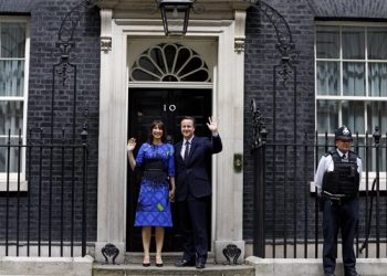 Britain's Prime Minister David Cameron and his wife Samantha wave from the steps of 10 Downing Street in London Friday, May 8, 2015 after meeting Britain's Queen Elizabeth II where he informed her  that he has enough support to form a government.  The Conservative Party swept to power Friday in Britain's Parliamentary elections winning an unexpected majority. (AP Photo/Kirsty Wigglesworth )