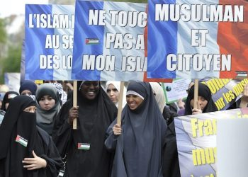 French muslim people hold banners reading 'do not touch my Islam' (C) and 'muslim and citizen' (R) during a demonstration in Paris, France on 02 April 2011, against islamophobia. ANSA/EMMA FOSTER