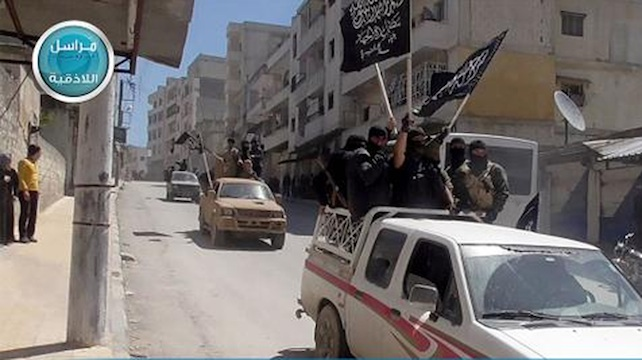 FILE - In this file photo posted on the Twitter page of Syria's al-Qaida-linked Nusra Front on Saturday, April 25, 2015, which is consistent with AP reporting, Nusra Front fighters stand on their vehicles and wave their group's flags as they tour the streets of Jisr al-Shughour, Idlib province, Syria. In Syria, al-Qaida's Nusra Front is the most powerful fighting force outside the territories held by the Islamic State group. Last month, it worked with other rebel factions, including ones backed by Saudi Arabia, Turkey and Qatar, to capture the northwestern city of Idlib and territory in the south _ the biggest victories in several years over President Bashar Assad.  (Al-Nusra Front Twitter page via AP, File)