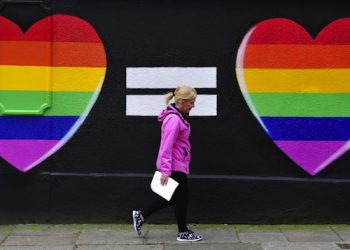 epaselect epa04761729 A woman walks past a mural of two hearts painted in rainbow colors, in Dublin, Ireland, 22 May 2015. Polling stations across Ireland have opened for the referendum on same-sex marriage, the first time a nationwide vote has been held on the issue. People may vote Yes or No to an amendment to the constitution which states, 'Marriage may be contracted in accordance with law by two persons without distinction as to their sex.'  EPA/AIDAN CRAWLEY