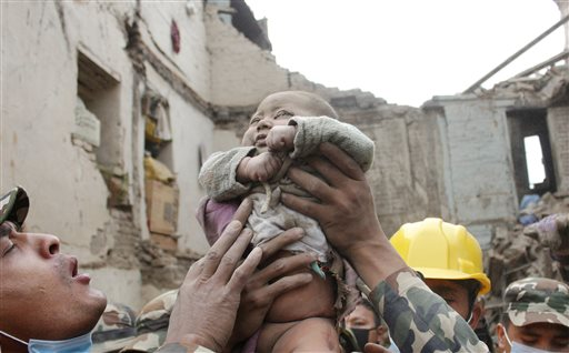 """In this Sunday, April 26, 2015, photo taken by Amul Thapa and provided by KathmanduToday.com, four-month-old baby boy Sonit Awal is held up by Nepalese Army soldiers after being rescued from the rubble of his house in Bhaktapur, Nepal, after Saturday's 7.8-magnitude earthquake shook the densely populated Kathmandu valley.  Thapa says that when he saw the baby alive after 20 hours of rescue efforts""""… all my sorrow went. Everyone was clapping. It gave me energy and made me smile in spite of lots of pain hidden inside me."""" (Amul Thapa/KathmanduToday.com via AP)"""