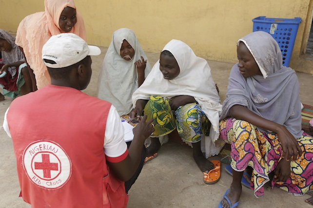 A Red Cross official takes data from women and children rescued by Nigerian soldiers from Boko Haram extremists at Sambisa Forest rest at a refugee camp in Yola, Nigeria Monday, May 4, 2015. Even with the crackle of gunfire signaling rescuers were near, the horrors did not end: Boko Haram fighters stoned captives to death, some girls and women were crushed by an armored car and three died when a land mine exploded as they walked to freedom.  (AP Photo/Sunday Alamba)