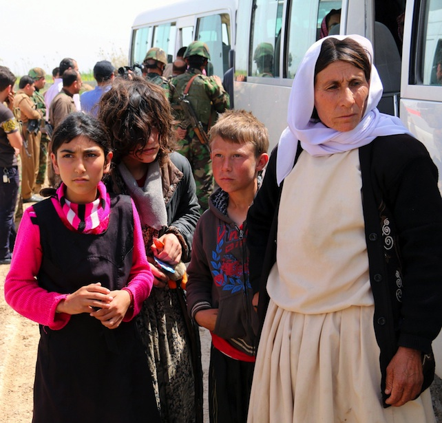 epa04695699 Iraqi Yazidis are seen at the entrance of a checkpoint in Kirkuk after their release by the Islamic State (IS) militant group near Kirkuk, northern Iraq, 08 April 2015. According to reports, Islamic State extremist group in Iraq released 216 Yazidis who had been held captive since last year. The group released largely consisted of women, children and the elderly. The Islamic State group attacked the Yazidi minority last year, taking hundreds of people hostages, including women allegedly used as sex slaves.  EPA/STR