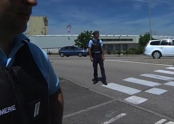 In this screen grab taken from video provided by BFM TV, police stand at the scene outside a factory where a man was allegedly beheaded, in Saint-Quentin-Fallavier, France,  Friday, June 26, 2015. French authorities have opened an investigation after an attack and explosion at a gas factory that left one person decapitated and several wounded. Banners with Arabic inscriptions were found near the body, an official said. (BFM TV via AP)