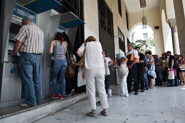 People line up at ATMs outside a National bank branch in the northern Greek port city of Thessaloniki, Monday, June 29, 2015.  Anxious Greeks lined up at ATMs as they gradually began dispensing cash again on the first day of capital controls imposed in a dramatic twist in Greece's five-year financial saga. Banks will remain shut until next Monday, and a daily limit of 60 euros ($67) has been placed on cash withdrawals from ATMs . (AP Photo/Giannis Papanikos)