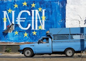 A man drives his van past a graffiti made by street artist N_Grams that read ''NO'' in German but also ''YES, IN'' in Greek language in Athens, on Sunday, June 28, 2015. Greece's parliament voted early Sunday in favor of Prime Minister Alexis Tsipras' motion to hold a July 5 referendum on creditor proposals for reforms in exchange for loans.(AP Photo/Petros Giannakouris)