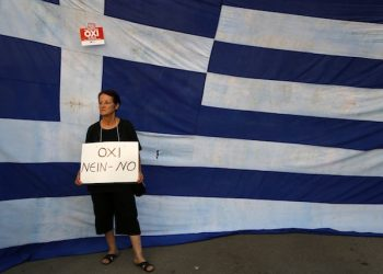 A supporter of a NO vote in the upcoming referendum, holds a placard reads ''NO'' during a rally at Syntagma square in Athens Monday, June 29, 2015. Anxious Greek pensioners swarmed closed bank branches and long lines snaked at ATMs as Greeks endured the first day of serious controls on their daily economic lives ahead of a July 5 referendum that could determine whether the country has to ditch the euro currency and return to the drachma. (AP Photo/Petros Karadjias)