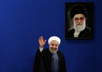 """Iran's President Hassan Rouhani waves to reporters at the conclusion of his press conference on the second anniversary of his election, in Tehran, Iran, Saturday, June 13, 2015. Rouhani said a final nuclear deal is """"within reach"""" as Iran and world powers face a June 30 deadline for an agreement. Rouhani said Iran will allow inspections of its nuclear facilities but vowed that the Islamic republic won't allow its state """"secrets"""" to be jeopardized under the cover of international inspections. A picture of the supreme leader Ayatollah Ali Khamenei hangs on the wall. (AP Photo/Ebrahim Noroozi)"""