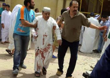 epa04819903 An injured man is helped following a blast at Imam Sadiq Mosque in al-Sawaber, Kuwait City, Kuwait, 26 June 2015. Thirteen people were killed and 25 injured in a suicide bombing at a Shiite mosque in Kuwait where worshippers had gathered for Friday prayers during the holy month of Ramadan, according to medics. The Islamic State group claimed the blast, according to a statement circulated on social media which could not be immediately verified.  EPA/RAED QUTENA ALTERNATIVE CROP