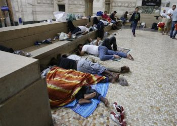 Migrants rest and sleep at Milan's main train station, Italy, early Friday morning, June 12, 2015. Milan city officials have appealed for help in managing the huge flow of migrants arriving from southern Italy after rescue at sea, as increasing numbers are unable to find beds and are sleeping in the train station. (AP Photo/Luca Bruno)