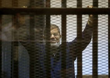 Egypt's ousted Islamist President Mohammed Morsi gestures in a defendants cage at the Police Academy courthouse in Cairo, Egypt, Tuesday, June 16, 2015. An Egyptian court on Tuesday confirmed a death sentence handed to Morsi over a mass prison break during the 2011 uprising that eventually brought him to power. On Tuesday a separate ruling upheld a life sentence for Morsi and confirmed death sentences against 16 others over charges of conspiring with foreign groups, including the Palestinian militant group Hamas. (AP Photo/Hassan Ammar)