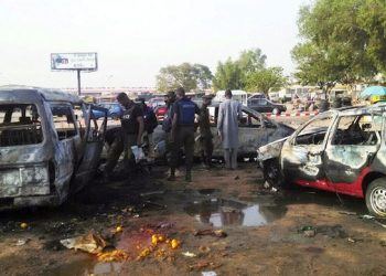 epa04637779 A picture made available on 26 February 2015 shows Nigerian police officers inspecting the scene of a bomb blast in Kano, Nigeria, 24 February 2015. According to reports at least 24 people were killed at two separate bus stations in Nigeria's north when teenage suicide bombers suspected to be affiliated to the terror group Boko Haram detonated their devices in the crowded stations.  EPA/STR BEST QUALITY AVAILABLE