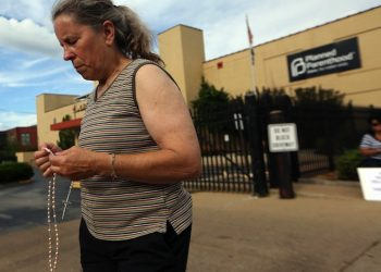 Mary Roy, of Potosi, Mo., holds a rosary in support of a pro-life rally, Tuesday, July 21, 2015, outside a Planned Parenthood building in St. Louis. Anti-abortion activists on Tuesday released a second undercover video aimed at discrediting Planned Parenthood's procedures for providing fetal tissue to researchers. (Laurie Skrivan/St. Louis Post-Dispatch via AP)
