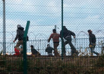 Migrants run on the railway as they attempt to access the Channel Tunnel, in Calais, northern France, Wednesday, July 29, 2015. Migrants rushed the tunnel linking France and England repeatedly for a second night on Wednesday and one man was crushed by a truck in the chaos, deepening tensions surrounding the thousands of people camped in this northern French port city. (AP Photo/Thibault Camus)