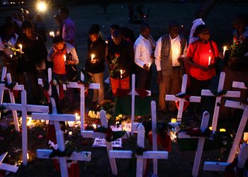 epa04695976 Kenya Red Cross team members hold candles and roses while standing in front of crosses on the ground as they attend the second day of candlelight vigil held for the 148 people killed in an attack on Garissa University College in Garissa town, in downtown Nairobi, Kenya, 08 April 2015. Hundreds of Kenyans continue to gather in solidarity to mourn the loss of their countrymen while five terror suspects were arraigned in a Nairobi court on 07 April for supplying attackers with guns used in an attack. Kenyan government on 08 April froze 85 bank accounts linked to suspected supporters of al-Shabab.  EPA/DANIEL IRUNGU