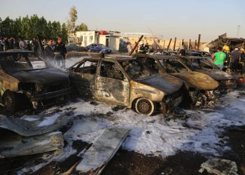 Security forces and civilians gather at the scene of a deadly car bomb in the Habibiya neighborhood of Sadr City, Baghdad,  Iraq, Saturday, Aug. 15, 2015. An Iraqi police official says the explosion at a popular car dealership in eastern Baghdad, that has been targeted multiple times in the past, has killed at least eight and wounded over a dozen people. (AP Photo/Karim Kadim)