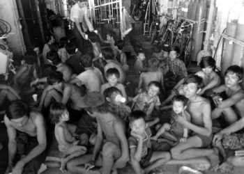 Vietnamese refugees rest as crewmen aboard the guided missile cruiser USS FOX (CG-33) give them something to drink.