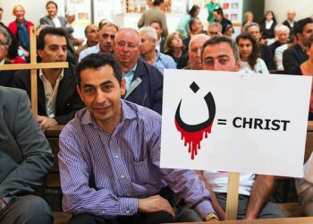 epa04357940 Believers take part in an Ecumenical Church Service for persecuted Christians in Iraq and Syria in the St. Hedwig Cathedral in Berlin, Germany, 17 August 2014. They hold a sign reading 'Christ' next to the Arabian letter 'n' for 'Nasara' which means Christians). This is the symbol that members of the Islamic State militia (IS) use to mark houses of Christians in Mossul in northern Iraq.  EPA/MAURIZIO GAMBARINI