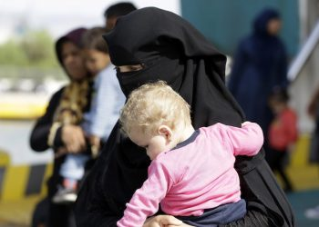 A woman holds a baby after their arrival from the northeastern Greek island of Lesbos to the Athens' port of Piraeus on Thursday, Sept. 10, 2015.  The European Council on Refugees and Exiles said Thursday that five EU countries are handling at least 70 percent of migrants seeking asylum in Europe. (AP Photo/Thanassis Stavrakis)