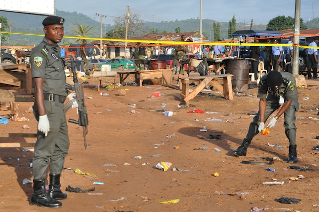 Police collect items at the site of a bomb explosion in Nyanya outskirt of Abuja, Nigeria, Saturday, Oct. 3, 2015.  Multiple bombs detonated in two locations killing at least 15 people, the National Emergency Management Agency said Saturday, although no group has claimed responsibility the attack has attributes of others by Boko Haram, the home-grown Islamic extremist group.(AP Photo/Gbenga Olamikan)