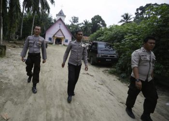 epa04978149 Police officers patrol an area close to a Church in Kuta Kerangan village, near Aceh Singkil, Indonesia, 15 October 2015. At least one person was killed and three churches were set ablaze during clashes between hundreds of hardliner Islamists and local Christians in the province of Aceh on 13 October 2015. The police said the attack followed Muslim residents' complaints about the presence of churches that they said lacked proper permits as places of worship. Local authorities promised to close the churches but locals were unhappy with negotiations over the issue, media said. Aceh is the only province in Indonesia that has been allowed to apply Islamic law as part of attempts by the central government to mollify desires for independence. A peace agreement between Jakarta and the Free Aceh Movement in 2005 ended a long-running separatist insurgency that claimed more than 15,000 lives, mostly civilians.  EPA/HOTLI SIMANJUNTAK