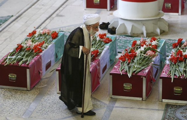 Senior Iranian cleric Ayatollah Ahmad Jannati, secretary of the Guardian Council, Iran's constitutional watchdog, walks past coffins of pilgrims who were killed in a stampede during the hajj pilgrimage in Saudi Arabia last month, during a funeral ceremony attended by thousands of mourners at Tehran University campus, Tehran, Iran, Sunday, Oct. 4, 2015. Iran has blamed Saudi authorities for the disaster, which heightened tensions between the two regional rivals. Saudi authorities say 769 pilgrims died in the stampede near Mecca in the worst disaster to strike the annual pilgrimage in a quarter-century. Iran appears to have lost the largest number of pilgrims, with 464 dead. (AP Photo/Vahid Salemi)