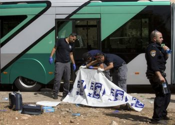 Israeli police officers examine the body of an Israeli at the scene of a shooting attack in Jerusalem, Tuesday, Oct. 13, 2015. A pair of Palestinian men boarded a bus in Jerusalem and began shooting and stabbing passengers, while another assailant rammed a car into a bus station before stabbing bystanders, in near-simultaneous attacks that escalated a monthlong wave of violence. Two Israelis and one attacker were killed.  (AP Photo/Sebastian Scheiner)