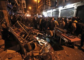 Lebanese army and civilians gather near the site of a twin suicide attack in Burj al-Barajneh, southern Beirut, Lebanon, Thursday, Nov. 12, 2015 that struck a Shiite suburb killed and wounded dozens, according to a Lebanese official. (AP Photo/Bilal Hussein)