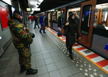 epa05040858 A Belgian soldiers observes the platform of a Brussels' metro station following the terror alert level being raised to 4/4, in Brussels, Belgium, 25 November 2015. Regular life began to return to Brussels on 25 November as schools reopened and underground train services partially resumed, despite the city remaining under maximum terrorism alert in the wake of the November 13 attacks on Paris. The Belgian capital has been under security alert level four since 21 November, due to what Belgian Prime Minister Charles Michel described as a 'serious and imminent threat.'  EPA/LAURENT DUBRULE