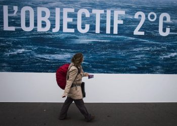 epa05022001 A woman walks in front of a poster bearing the message 'Objective 2 degrees' in reference to the projected agreement to limit the increase of global warming to two degrees Celsius, in Paris, France, 12 November 2015. France will host the COP21 Climate Change Conference from 30 November to 11 December 2015.  EPA/IAN LANGSDON
