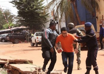 Mali trooper assist a hostage, centre, to leave the scene, from the Radisson Blu hotel to safety after gunmen attacked the hotel in Bamako, Mali, Friday, Nov. 20, 2015. Islamic extremists armed with guns and throwing grenades stormed the Radisson Blu hotel in Mali's capital Friday morning, killing at least three people and initially taking numerous hostages, authorities said.  (AP Photo/Harouna Traore)