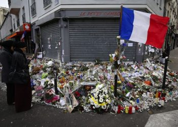epa05035825 People gather in front of the memorial set near the Le Petit Cambodge restaurant to mark a week since the start of the terrorist attacks, in Paris, France, 21 November 2015. More than 130 people were killed and hundreds injured in the terror attacks which targeted the Bataclan concert hall, the Stade de France national sports stadium, and several restaurants and bars in the French capital on 13 November.  EPA/SEBASTIEN NOGIER