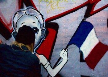La resistenza passa anche attraverso i graffiti. E fa da contraltare pi˘ creativo e colorato alla piazza della memoria per eccellenza, quella place de la Republique che a distanza di 10 mesi dalla strage di Charlie Hebdo, si Ë riempita di nuovo di candele, fiori e bigliettini. Dall'altro lato della piazza, su un muro di compensato usato da mesi come 'tela' dai writers, ci sono i pensieri 'di pancia' dei parigini pi˘ giovani. Un gruppetto di loro si Ë ritrovato lÏ nel pomeriggio con bombolette e pennelli per lasciare le proprie tracce di resistenza. E' il caso della scritta gigantesca, su sfondo nero, che riprende il motto di Parigi (il latino 'Fluctuat nec mergitur', naviga e non affonda) compreso lo stemma della nave. Oppure il graffito pi˘ naif dominato dalla scritta 'Pray for Paris' e accanto il simbolo della pace stilizzato con la torre Effeil. Pi˘ immediato lo slogan 'No pasaran', che ha avuto i complimenti anche di un poliziotto che passava di lÏ. L'unica writer della piazza ha scelto un disegno pi˘ elaborato: un bambino con i lacrimoni che tiene in mano una bandiera della Francia, macchiata di sangue. Sotto, onde nere e attorno note musicali insanguinate, tanto per non scordare quel concerto al teatro Bataclan sporcato da violenza e morte. ANSA/MICHELA SUGLIA