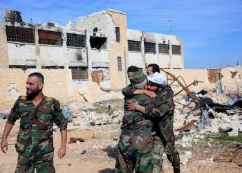 In this photo released by the Syrian official news agency SANA, shows Syrian government troops hug each other in celebration inside the Kweiras air base, east of Aleppo, Syria, Wednesday, Nov. 11, 2015. Syrian government forces broke a siege imposed by the Islamic State group on the northern military air base of Kweiras since 2013. The international community is mounting its most serious effort yet to end the nearly five-year-old Syrian war, rallying around a second round of talks in Vienna this week amid the emergence of a Russian proposal that calls for early elections. (SANA via AP)