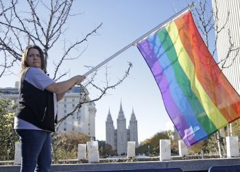 Sandy Newcomb poses for a photograph with a rainbow flag as Mormons gather for a mass resignation from the Church of Jesus Christ of Latter-day Saints Saturday, Nov. 14, 2015, in Salt Lake City. A day after the Mormon church stood behind its new rules targeting gay members and their children, while issuing clarifications, hundreds held a rally in Salt Lake City to protest their displeasure with the policy changes. (AP Photo/Rick Bowmer)