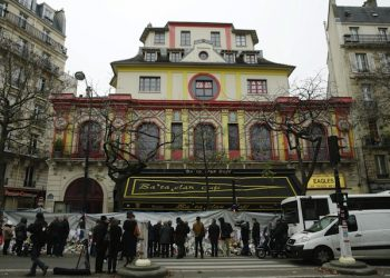 epa05044407 People pay their respect in front of the Bataclan concert place during the national memorial service to pay homage to the victims of the November 13 terrorist attacks, in Paris, France, 27 November 2015. 130 people were killed and hundreds injured in the terror attacks which targeted the Bataclan concert hall, the Stade de France national sports stadium, and several restaurants and bars in the French capital on 13 November 2015.  EPA/YOAN VALAT