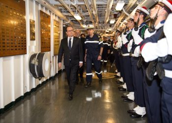 This photo released on Friday, Dec. 4, 2015 by the French Army Communications Audiovisual office (ECPAD) shows France's President, Francois Hollande, left, reviewing an honor guard upon his arrival aboard the Charles De Gaulle aircraft carrier operating off Syria in the Mediterranean sea. French President Francois Hollande is visiting the aircraft carrier launching airstrikes against the Islamic State group. The Charles de Gaulle has launched raids against Islamic State bases since the Nov. 13 attacks that killed 130 in Paris. (Christian Cavallo/ECPAD via AP)     THIS IMAGE MAY ONLY BE USED FOR 30 DAYS FROM TIME TRANSMISSION.