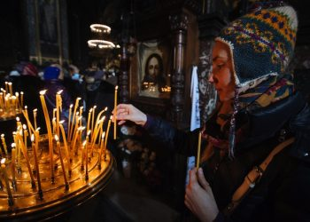 epa04548929 A woman lights a candle during the Orthodox Christmas Eve mass in St. Volodymir cathedral, Kiev, Ukraine, 06 January 2015. Christian Orthodox believers celebrate Christmas according to the Julian calendar on 06 January.  EPA/ROMAN PILIPEY