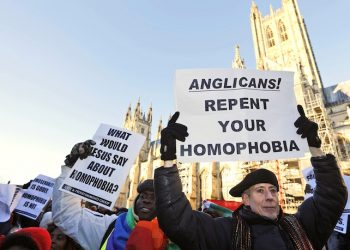Human rights campaigner Peter Tatchell, right, demonstrates with others against the decision by Anglican Primates to punish pro-gay equality churches in North America, in front of the Canterbury Cathedral in Canterbury, England, Friday, Jan. 15, 2016. Anglican spiritual leader Justin Welby is set to lead a task force that will focus on rebuilding relationships after religious leaders temporarily restricted the role of the Episcopal Church in their global fellowship as a sanction over the U.S. church's acceptance of gay marriage. Welby, the Archbishop of Canterbury, is expected Friday to explain the decision to bar Episcopalians from any policy-setting positions in the Anglican Communion for three years. The decision avoided a permanent split in the 85 million-member communion, though it dismayed liberal Anglicans. (AP Photo/Frank Augstein)