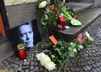 epa05096986 Flowers and candles have been placed around a photo of David Bowie in front of the singer's former residence at Hauptstrasse 155 in†Berlin, Germany, 11 Janaury 2016.  A card which was placed between the flowers reads 'For David, Thank you for the music!'. Bowie. According to reports quoting David Bowie's son and his official Facebook page, Bowie, 69, has died on 10 January 2016 after a battle with cancer. 'David Bowie died peacefully surrounded by his family after a courageous 18 month battle with cancer. While many of you will share in this loss, we ask that you respect the family's privacy during their time of grief,' read a statement posted on the artist's official social media accounts.  EPA/JENS KALAENE