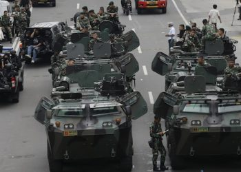 Indonesian soldiers man armored vehicles as they guard near the site where an attack occurred in Jakarta, Indonesia Thursday, Jan. 14, 2016. Attackers set off explosions at a Starbucks cafe in a bustling shopping area in Indonesia's capital and waged gunbattles with police Thursday, leaving bodies in the streets as office workers watched in terror from high-rise windows. (AP Photo/Achmad Ibrahim)