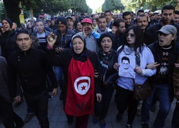 epa05116260 Unemployed graduates shout slogans during a demonstration urging the government to provide them with job opportunities, in Tunis, Tunisia, 21 January 2016. Reports state one policeman was killed in clashes between security forces and protesters demanding jobs in Tunisia's western-central province of Kasserine, a security official said on 21 January. The protests in Kasserine started at the weekend after an unemployed young man reportedly suffered a deadly electric shock when he climbed a power pole to protest a rejected job application.  EPA/MOHAMED MESSARA
